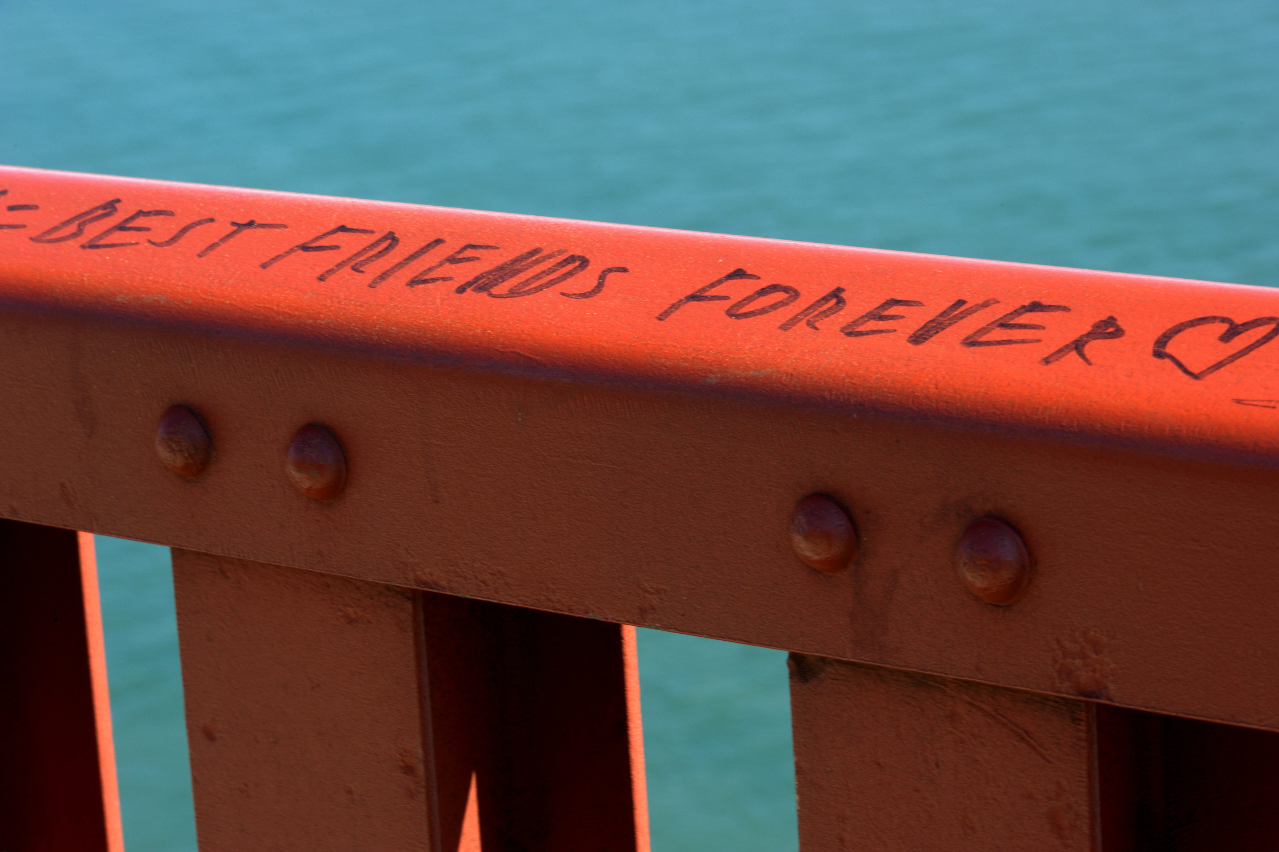 "Guard rail along the east sidewalk of the Golden Gate Bridge in San Francisco, California. A permanent marker inscription reads ""Best friends forever ?""."